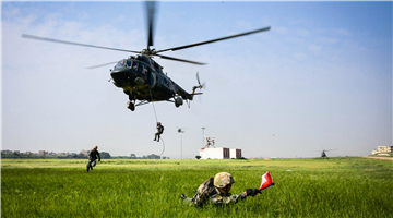 Soldiers fast-rope from Mi-171 transport helicopters