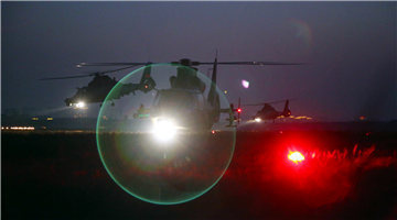 Attack helicopters lift off at night