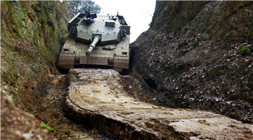 Type-96 MBTs pass through shallow trench