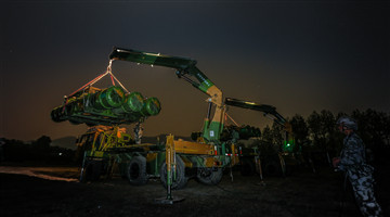 Soldiers load air-defense missile systems at night