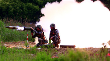 Soldiers fire portable anti-tank rocket launchers